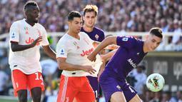 Bek Fiorentina, Nikola Milenkovic, berebut bola dengan striker Juventus, Cristiano Ronaldo, pada laga Serie A di Stadion Artemio Franchi, Florence, Sabtu (14/9). Kedua klub bermain imbang 0-0. (AFP/Vincenzo Pinto)