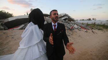 Mohammed Zourab (kanan) bersama pengantin perempuannya menggelar pernikahan di atas reruntuhan rumahnya di Kota Khan Younis, Jalur Gaza, 1 Maret 2020. Upacara pernikahan warga Palestina digelar di atas reruntuhan salah satu rumah yang hancur akibat serangan jet Israel. (Xinhua/Khaled Omar)