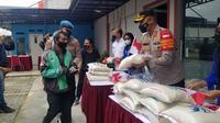Driver ojol menerima bantuan dari Aliansi Mahasiswa dan Aktivis Nasional (AMAN) Indonesia yang dibantu oleh personel polri di Tangerang. (Liputan6.com/Pramita Tristiawati)