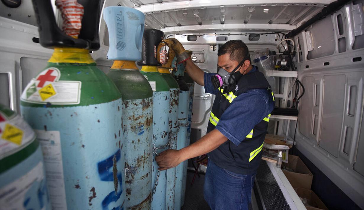 Petugas kesehatan Jose Antonio Pena mengisi ulang tangki oksigen untuk pasien COVID-19 di Distrik Iztapalapa, Mexico City, Meksiko, Selasa (26/1/2021). Mexico City menawarkan isi ulang oksigen gratis untuk pasien COVID-19. (AP Photo/Marco Ugarte)