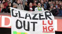 Fans MU menggelar spanduk protes anti-Glazer di laga lanjutan EPL antara MU vs Portsmouth yang digelar di Old Trafford, 6 Februari 2010. AFP PHOTO / ANDREW YATES