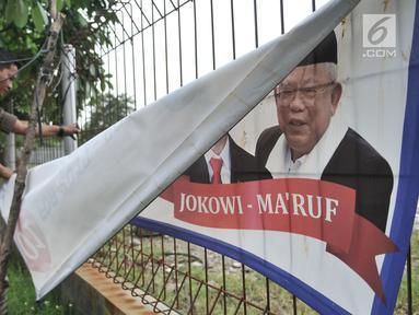 Petugas Satpol PP mencopot spanduk APK di sepanjang Jalan Yos Sudarso, Jakarta Utara, Rabu (13/3). Bawaslu menginstruksikan Pemkot se-DKI Jakarta untuk menertibkan APK yang dipasang di sembarang tempat dan fasilitas umum. (merdeka.com/Iqbal S. Nugroho)