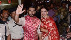 Pasangan pengantin baru, Ranveer Singh dan Deepika Padukone menyapa penggemar yang menyambut mereka di bandara internasional Mumbai, Minggu (18/11). Pasangan bintang Bollywood India itu baru saja kembali dari acara pernikahan mereka di Italia. (AFP)