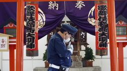 Seorang petugas keamanan yang mengenakan masker pelindung untuk membantu mengekang penyebaran virus corona COVID-19 berjalan di depan sebuah kuil di Tokyo, Jepang, Kamis (15/4/2021). Tokyo mengonfirmasi lebih dari 700 kasus baru COVID-19 pada 15 April 2021. (AP Photo/Eugene Hoshiko)