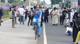 Seorang warga bersepeda di antara peserta Reuni 212 saat Car Free Day (CFD) di kawasan Jakarta, Minggu (2/12). Warga tetap memadati area Car Free Day  dari Bundaran HI-Sudirman meskipun ada aksi Reuni 212. (Liputan6.com/Angga Yuniar)