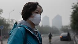 Seorang wanita beraktivitas mengenakan masker pelindung untuk menghindari polusi udara buruk di Beijing (22/10). (AFP Photo/Nicolas Asfaouri)
