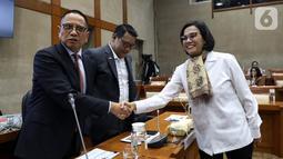 Menteri Keuangan Sri Mulyani (kanan) bersalaman dengan Ketua Komisi XI DPR RI Dito Ganinduto sebelum rapat kerja di Gedung Nusantara I, Jakarta, Senin (4/11/2019). Rapat membahas mengenai evaluasi kinerja 2019 dan rencana kerja 2020. (Liputan6.com/JohanTallo)