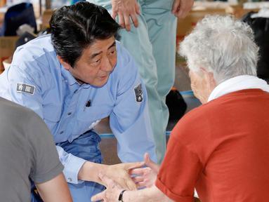 PM Jepang, Shinzo Abe berbincang dengan warga korban banjir saat mengunjungi lokasi penampungan di Kurashiki, Prefektur Okayama, Rabu (11/7). Korban tewas akibat bencana banjir di Jepang meningkat menjadi 179 jiwa. (Shohei Miyano/Kyodo News via AP)