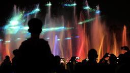 Pengunjung menyaksikan keindahan air mancur menari di sebuah taman di Warsawa, Polandia, 1 Mei 2018. Pertunjukan seni air mancur ini berlangsung setiap awal musim semi dimulai dengan durasi selama 30 menit. (AP/Alik Keplicz)