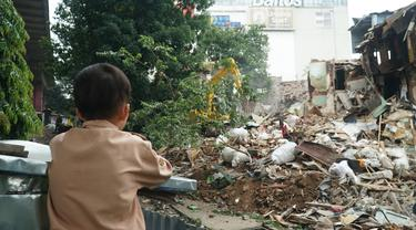 Seorang bocah menyaksikan alat berat yang digunakan Satpol PP Kota Bandung untuk meratakan tanah di lahan proyek rumah deret. (Liputan6.com/Huyogo Simbolon)