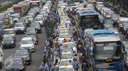 Deretan taksi terlihat diparkir di jalur Transjakarta di Jalan Gatot Subroto, Jakarta, Selasa (22/3). Ribuan sopir taksi memblokir jalan protokol tersebut hingga menyebabkan kemacetan total di kawasan itu. (Liputan6.com/Immanuel Antonius)