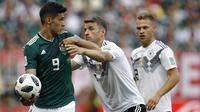 Gelandang Jerman, Thomas Mueller, berusaha merebut bola dari striker Meksiko, Raul Jimenez, pada laga Grup F Piala Dunia di Stadion Luzhniki, Moskow, Minggu (17/6/2018). Meksiko menang 1-0 atas Jerman. (AP/Victor Caivano)