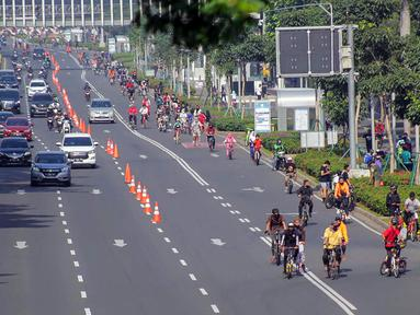 Warga berolahraga menggunakan sepeda di sepanjang Jalan Sudirman, Jakarta, Minggu (26/7/2020). Pemprov DKI menyiapkan 30 kawasan khusus pesepeda di lima kota administrasi Jakarta. (Liputan6.com/Faizal Fanani)