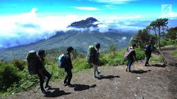 Para pendaki melintasi pemandangan Gunung Merapi dari atas Gunung Merbabu di Selo, Boyolali, Jawa Tengah, Sabtu (2/2/2019). Aktivitas Gunung Merapi dalam beberapa hari terakhir masih tinggi dan masih berada di level 2 atau waspada. (Merdeka/Arie Basuki)