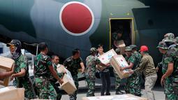 Personil militer Jepang dibantu TNI mengangkut bantuan logistik dari pesawat kargo AU Jepang di bandara Mutiara Sis Al-Jufri, Palu, Sulteng (6/10). Bantuan ini  untuk para korban gempa dan tsunami yang menewaskan 1500 jiwa. (AP Photo/Tatan Syuflana)