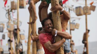 Seorang peserta berusaha menahan rekannya saat mengikuti lomba panjat pinang selama perayaan HUT ke-74 RI di Pantai Ancol, Jakarta, Sabtu (17/8/2019). Indonesia merayakan kemerdekaan yang ke-74 dari pemerintahan kolonial Belanda. (AP Photo/Tatan Syuflana)