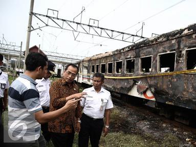 Menhub Budi Karya menyimak keterangan warga saat meninjau lokasi terbakarnya dua gerbong kereta Kerta Jaya kelas Ekonomi di dekat Stasiun Tanjung Priok, Jakarta, Kamis (25/8). (Liputan6.com/Faizal Fanani)