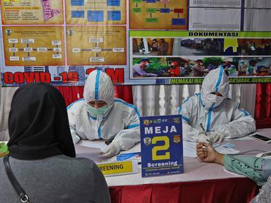 Petugas melakukan penyaringan (screening) kepada peserta vaksinasi COVID-19 di Kampung Tangguh Jaya Cideng, Jakarta, Sabtu (10/4/2021). Kapolda Metro Jaya, Irjen Pol M Fadil Imran, menargetkan program vaksinasi massal ini selama enam bulan ke depan. (Liputan6.com/Herman Zakharia)