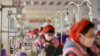 Pekerja Pabrik Pakaian Rajut Songyo membuat masker untuk perlindungan terhadap coronavirus baru di Pyongyang (6/2/2020). Setidaknya 31.000 orang telah terinfeksi dan lebih dari 630 orang meninggal akibat virus tersebut. (AFP/Kim Won-Jin)