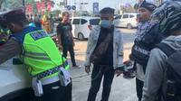Seorang pengendara motor pura-pura kesurupan saat diminta putar balik oleh petugas kepolisian di pos penyekatan jalur arteri di kawasan Padalarang, Kabupaten Bandung Barat pada Selasa (11/5/2021).