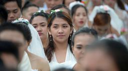 Ekspresi seorang wanita saat bersiap mengikuti pernikahan massal sebagai bagian dari perayaan Hari Valentine di Manila, Filipina (14/2). Sekitar 200 pasangan dilaporkan ikut serta dalam acara tersebut. (AFP Photo/Ted Aljibe)