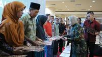 Wali Kota Surabaya Tri Rismaharini menyerahkan bantuan dana perbaikan rumah kepada warga korban musibah kebakaran yang terjadi di Jalan Margorukun Gang Lebar, Kelurahan Gundih, Surabaya (Foto:Liputan6.com/Dian Kurniawan)