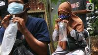 Warga meniupkan kantong saat menjalani tes deteksi COVID-19 dengan metode GeNose C19 usai terjaring razia penggunaan masker di Kelurahan Sudimara Barat, Kota Tangerang, Kamis (27/5/2021). Tes tersebut untuk menekan penyebaran corona di wilayah tersebut. (Liputan6.com/Angga Yuniar)