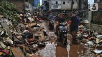 Pengendara sepeda motor melintas saat warga membersihkan sampah sisa banjir di Kebalen, Jakarta, Minggu (21/2/2021). Banjir yang terjadi kemarin karena curah hujan yang tinggi meninggalkan sampah di rumah warga. (Liputan6.com/Johan Tallo)