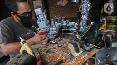 Animator Toto Sihono, membuat produk berupa pajangan dari limbah komponen elektronik di Galeri Artos Griya Asri Pamulang, Tangerang Selatan, Rabu (16/8/2020). Produk dari limbah elektronik yang digeluti sejak tahun 2016 dijual dengan harga Rp250 - 350 ribu perbuah. (Liputan6.com/Fery Pradolo)
