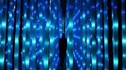 """Seorang pengunjung berjalan melintasi instalasi cahaya yang berjudul 'Vines' pada sesi pemotretan di Kew Gardens, London, Selasa (19/11/2019). Pemasangan lampu tersebut untuk menyambut Natal dan peluncuran acara """"Christmas at Kew Gardens"""". (Daniel LEAL-OLIVAS / AFP)"""