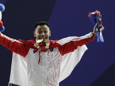 Lifter Eko Yuli melakukan selebrasi saat mendapatkan medali emas SEA Games 2019 cabang angkat besi nomor 61 kg di Stadion Rizal Memorial, Manila, Minggu (1/12). Dirinya meraih emas dengan total angkatan 309 kg. (Bola.com/M Iqbal Ichsan)