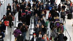 Antrean wisatawan untuk melakukan check in di Bandara Internasional John F. Kennedy, New York, Rabu (21/11). Masyarakat Amerika mulai bergegas pulang ke kampung halamannya alias mudik untuk merayakan Thanksgiving Day. (AP/Mark Lennihan)