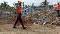 Polisi dengan bantuan anjing pelacak bersiap mencari korban gempa bumi di bangunan Rumah Sakit Mitra Manakarra yang runtuh di Mamuju, Minggu (17/1/2021). Polri mengerahkan enam ekor K-9 untuk membantu menangani dampak gempa bumi di Majene dan Mamuju, Sulawesi Barat. (Liputan6.com/Abdul Rajab Umar)