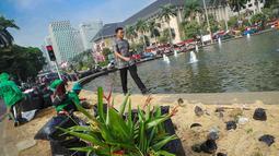 Petugas dinas pertamanan membersihkan Taman Silang Monas yang rusak akibat injakan massa Prabowo, Jakarta, Jumat (22/8/14). (Liputan6.com/Faizal Fanani)