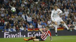 Tembakan keras Cristiano Ronaldo melewati adangan pemain Athletic Bilbao, Unai Nunez pada lanjutan La Liga Santander di Santiago Bernabeu stadium, Madrid, (18/4/2018). Real Madrid bermain imbang 1-1 dengan Bilbao. (AP/Francisco Seco)