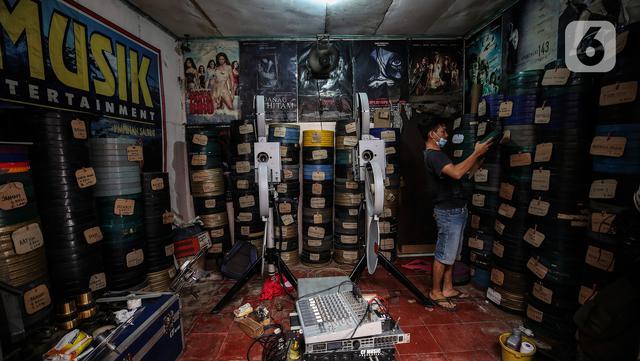Adul (29) mencari film seluloid 35mm untuk pertunjukan layar tancap di gudang rumahnya di Jakarta, Rabu (28/4/2021). Sambil sesekali saat alat bisa digunakan mereka menggelar layar tancap untuk menghibur warga di lingkungan mereka saja. (Liputan6.com/Johan Tallo)