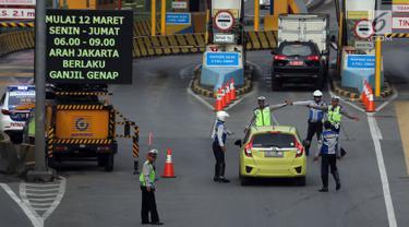 Polisi dan petugas Dishub memberi arahan kepada pengendara mobil di depan Gerbang Tol Bekasi Barat 1, Bekasi, Jawa Barat, Senin (12/3). Peraturan ganjil genap ini berlaku mulai hari ini, Senin (12/3) pukul 06.00-09.00. (Liputan6.com/Arya Manggala)