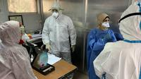 Anggota tim pakar medis China, Yang Honghui (kanan) memasuki Laboratorium Kesehatan Masyarakat Pusat di Baghdad, Irak, Kamis (26/3/2020). Sejak 7 Maret lalu, tujuh pakar medis China bekerja sama dengan tenaga ahli lokal di Irak untuk memerangi epidemi virus corona COVID-19. (Xinhua)