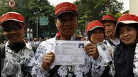 Seorang guru honorer menunjukan kartu peserta ujian CPNS saat melakukan unjuk rasa di Jl.Asia Afrika, Senayan, Jakarta, Selasa (15/9/2015). Ribuan guru honorer menuntut perubahan status guru honorer K2 menjadi PNS. (Liputan6.com/Yoppy Renato)