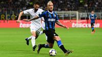Gelandang Inter Milan, Radja Nainggolan berebut bola dengan pemain Empoli Marko Pajac pada pertandingan pekan ke-38 Serie A di Giuseppe Meazza, Minggu (26/5/2019). Inter Milan akhirnya lolos ke Liga Champions musim depan setelah bersusah payah menyegel kemenangan 2-1 atas Empoli. (Miguel MEDINA/AFP)