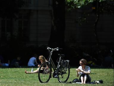 Seorang wanita bersantai di bawah sinar matahari di Victoria Tower Gardens dekat Gedung Parlemen di London, Inggris (23/7/2019). Suhu melonjak di atas 30C (86F) di Inggris pada 23 Juli dengan para peramal cuaca memperkirakan suhu setinggi 37C (96.8F) sebelum akhir pekan. (AFP Photo/Ben Stansall)