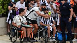 Dalam kesempatan tersebut, Cristiano Ronaldo menyempatkan waktunya untuk menyapa penggemar yang sudah menunggu diluar. dan tanpa diduga dirinya menghampiri penggemarnya yang duduk di kursi roda dan melakukan swafoto bersama. (Foto: AFP/Miguel Medina)