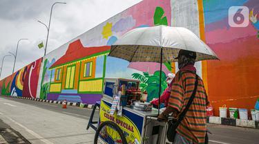 "Seorang pedagang melintasi mural yang dibuat di Flyover Gaplek, Tangerang Selatan, Rabu (10/3/2021). Konsep muralnya adalah ""Tangsel Membangun"". (Liputan6.com/Faizal Fanani)"