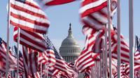 Capitol AS terlihat di antara bendera-bendera yang ditempatkan di National Mall menjelang pelantikan Presiden terpilih Joe Biden di Washington, Senin (18/1/2021). Acara pengambilan sumpah Joe Biden  akan berada dalam situasi berbeda dari pelantikan-pelantikan sebelumnya. (AP Photo/Alex Brandon)