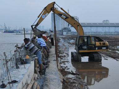 Alat berat dikerahkan untuk menyelesaikan proyek pembangunan tanggul di Pantai Muara Baru, Jakarta, Rabu (2/12). Proyek tanggul tersebut bertujuan untuk menahan banjir rob yang sering melanda kawasan Muara Baru. (Liputan6.com/Gempur M Surya)