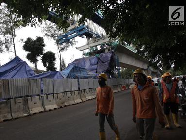Pekerja melintas dekat kontruksi beton proyek light rapid transit ( LRT)  yang roboh di Kayu Putih, Jakarta Timur, Senin (22/1). Akibat robohnya konstruksi beton proyek LRT ini setidaknya lima orang yang mengalami luka-luka. (Liputan6.com/Arya Manggala)