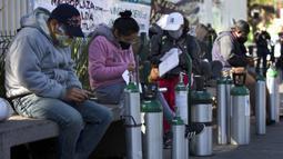 Orang-orang menunggu untuk mengisi ulang tangki oksigen bagi kerabat mereka yang menderita COVID-19 di Distrik Iztapalapa, Mexico City, Meksiko, Selasa (26/1/2021). Mexico City menawarkan isi ulang oksigen gratis untuk pasien COVID-19. (AP Photo/Marco Ugarte)