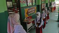 Sejumlah murid menerapkan jaga jarak sebelum masuk ke sekolah di SD Negeri 6, Bekasi, Jawa Barat, Selasa (4/8/2020). Pemerintah setempat memberikan izin kepada enam sekolah untuk melakukan uji coba pembelajaran tatap muka selama satu bulan. (Liputan6.com/Herman Zakharia)