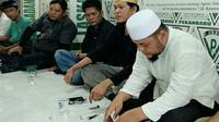 Joni Boy (tengah) ketika dibawa FPI Pekanbaru setelah menghina UAS. (Liputan6.com/M Syukur)