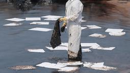Penjaga pantai Sri Lanka mengenakan pakaian khusus saat membersihkan tumpahan minyak di sebuah pantai di Uswetakeiyawa, Kolombo, Senin (10/9). Tumpahan minyak disebabkan oleh kebocoran pipa. (AP Photo/Eranga Jayawardena)